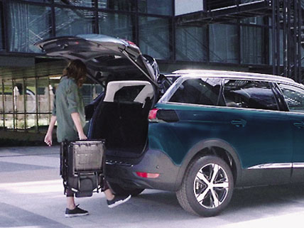 Woman loading surfboard into Peugeot 5008 SUV with hands free tailgate